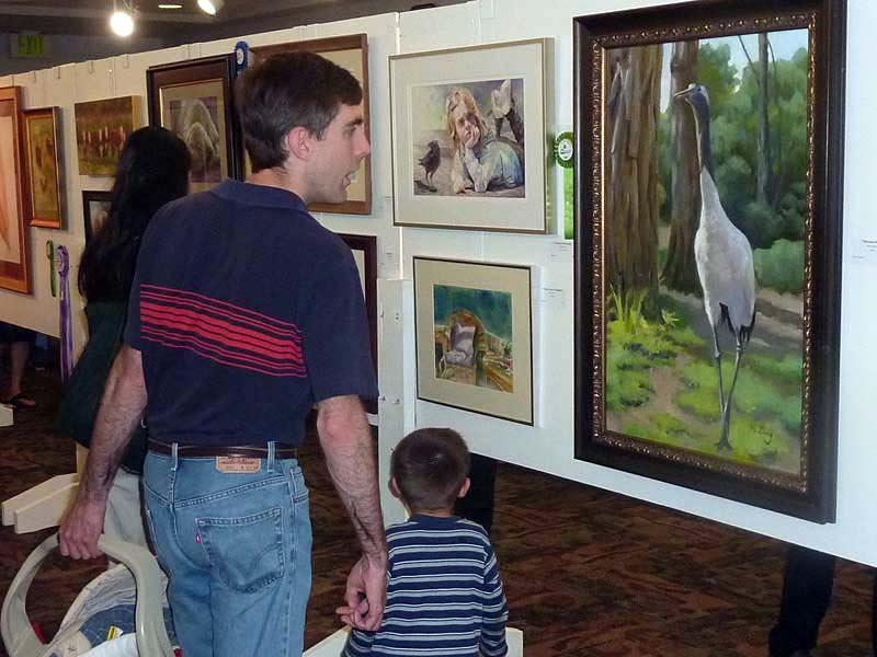 Man and little boy looking at the art work of the 2011 Arts of the Terrace Juried Art Show.