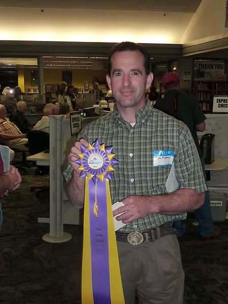 Joel Rummell holding champion ribbon at the 2011 Arts of the Terrace Juried Art Show..
