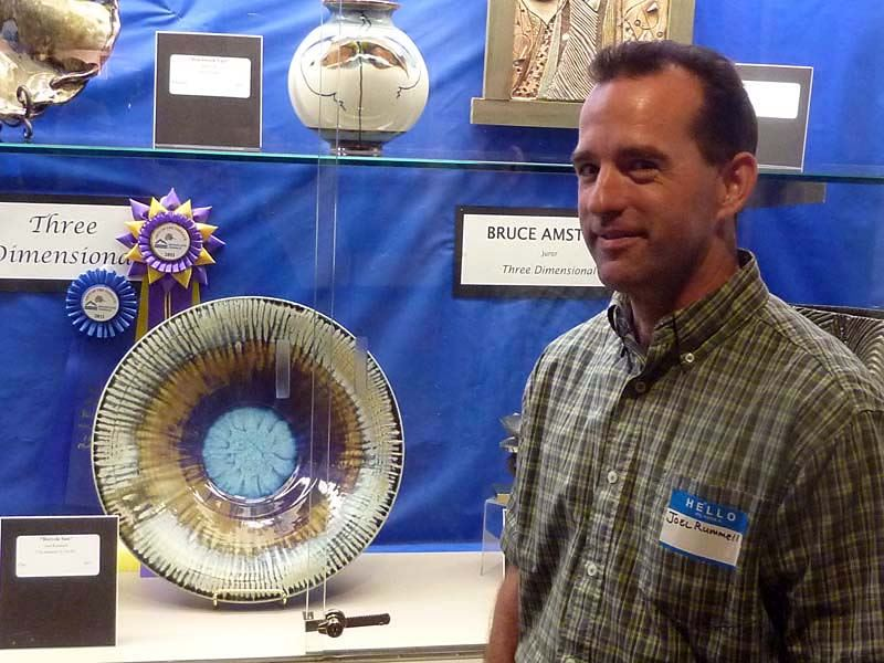 Joel Rummell standing next to his prize winning ceramic piece.