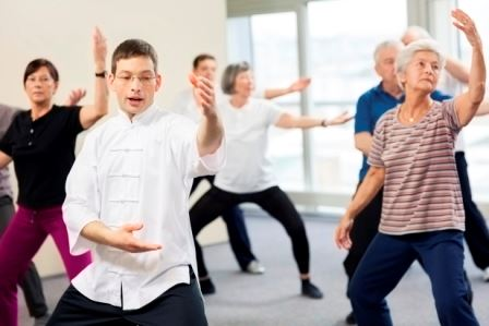 Group of Retired people practicing Tai Chi with instructor