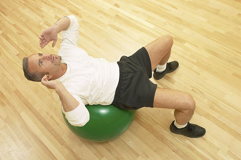Man on a thera ball doing crunches