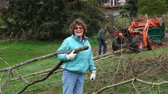 Volunteer cleaning up tree waste.