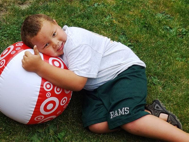 A little boy snuggles up to his beach ball.