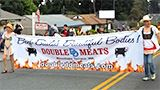 "People carrying the Double Meats ""Beef Builds Beautiful Bodies"" banner."