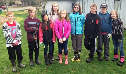 Nine Brighton School Volunteers with garden gear smiling for camera