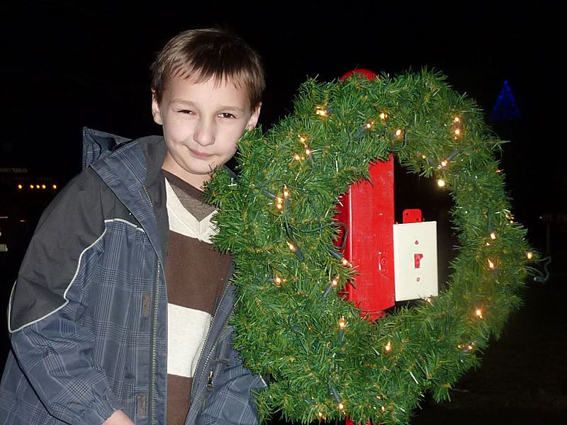 Little boy poses next to a wreath.