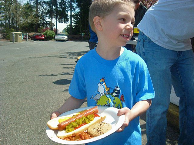 Little boy getting ready to enjoy his hotdog and cookie.