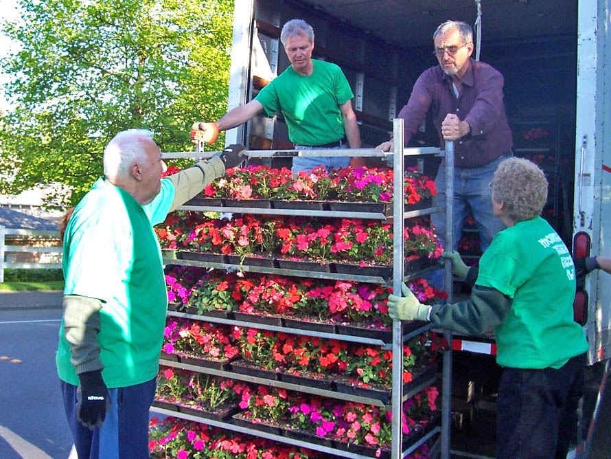 Members of the Garden Club unload a cart of flowers.