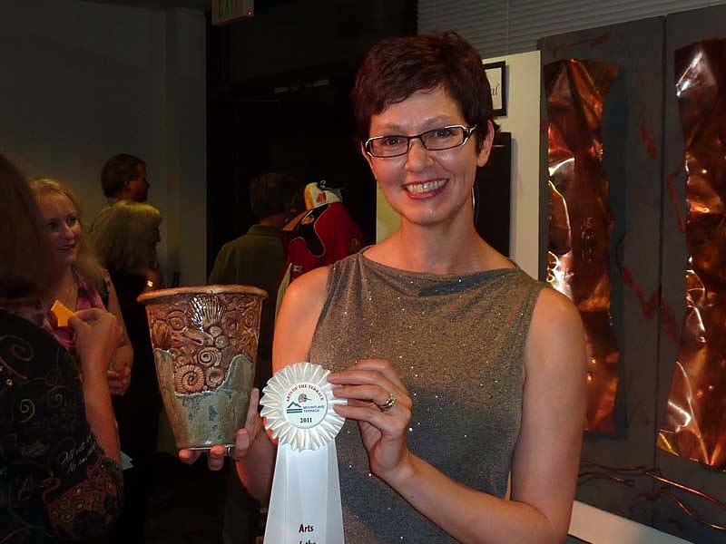 Woman holding a white ribbon and her clay vessel at the 2011 Arts of the Terrace Juried Art Show.