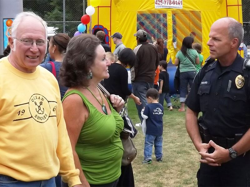 A couple speaking with a police officer at the 2012 National Night Out celebration.