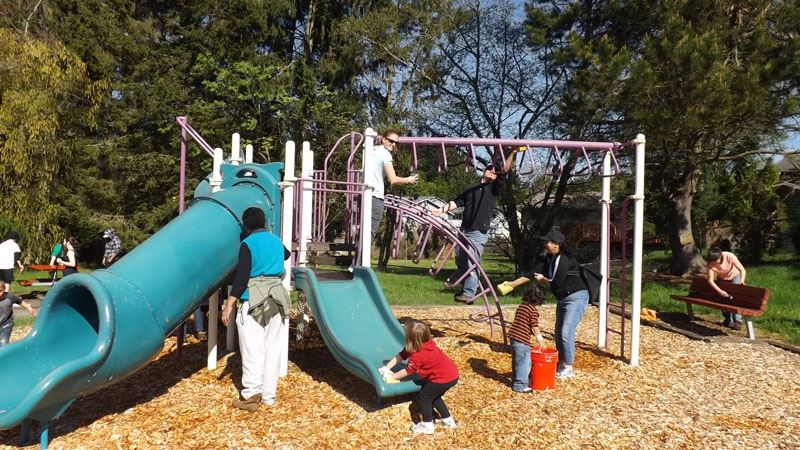 Children and parents volunteer to help clean up play equipment.